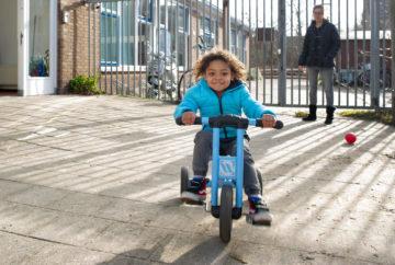 Fietsend over het plein rijden bij kinderdagverblijf - Up Kinderopvang aan de Daniël Catterwijckstraat in Rijswijk