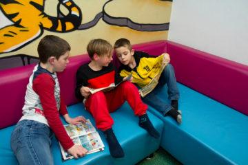 Lezen en kletsen op de bank bij buitenschoolse opvang - Up Kinderopvang aan ILSY-plantsoen Den Haag Ypenburg