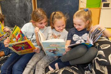 Samen lezen op de bank bij buitenschoolse opvang - Up Kinderopvang aan Laan van Hoornwijck In den Haag Ypenburg