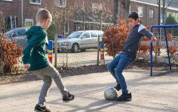 Voetballen op het plein bij buitenschoolse opvang - Up Kinderopvang aan de Willem van Rijswijckstraat in Rijswijk